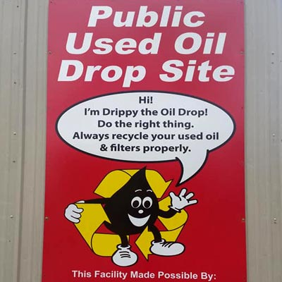 Sign on Albany Recycling Center's building promoting that they are an official Pubic Used Oil Drop Site