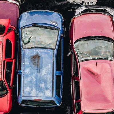 Aerial photo of old cars piled up in a scrap yard waiting to be recycled
