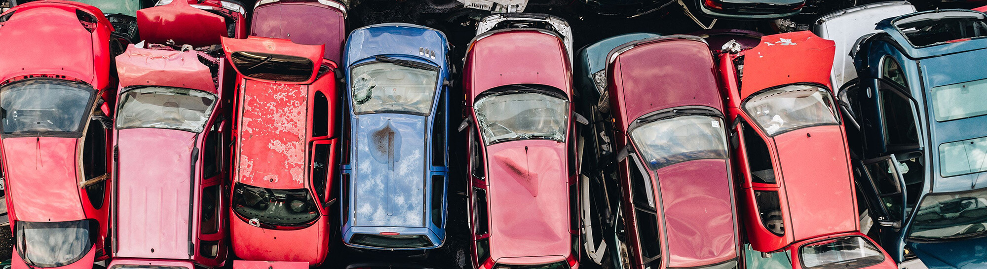 Aerial photo of rows of scrapped cars, trucks and vans